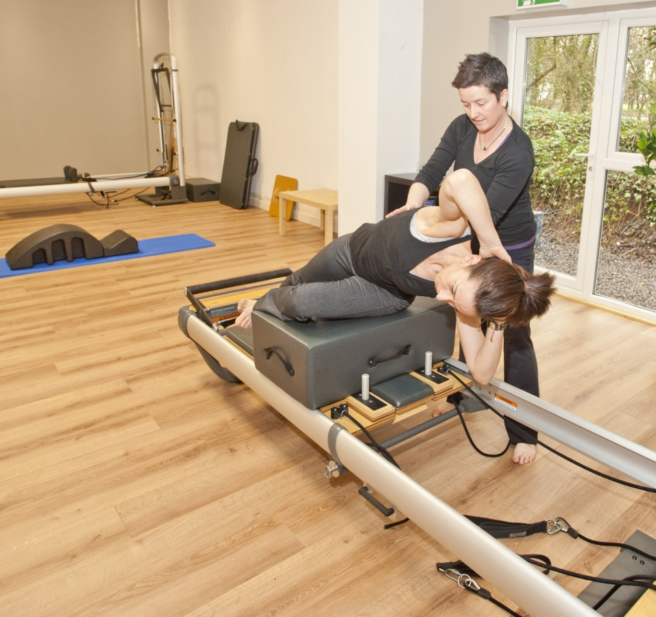 Karen Ingram teaching client at Reformer
